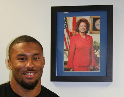 Nolan Carroll stands beside a picture of his mother, Florida Lt. Gov. Jennifer Carroll